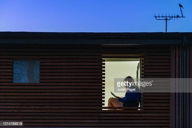 teenage girl wearing mask sitting in her window - solitude stock pictures, royalty-free photos & images