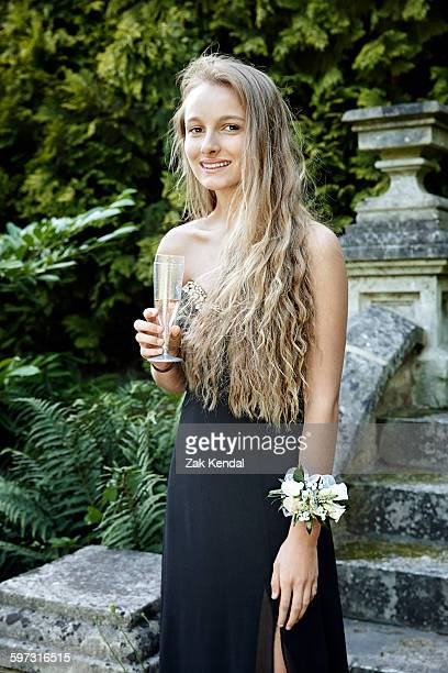 Teenage girl wearing prom dress and corsage holding champagne flute looking at camera smiling