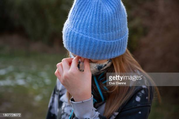 teenage girl wearing protective face mask and rubbing bridge of nose in tension - long hair stock pictures, royalty-free photos & images