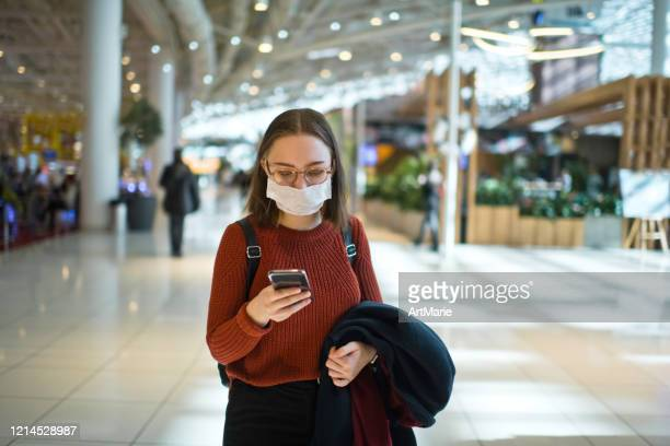 teenage girl wearing protective face mask in a public place - shopping centre stock pictures, royalty-free photos & images