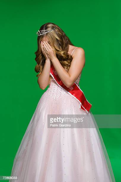 Teenage girl (16-17) wearing sash and tiara, hands covering face
