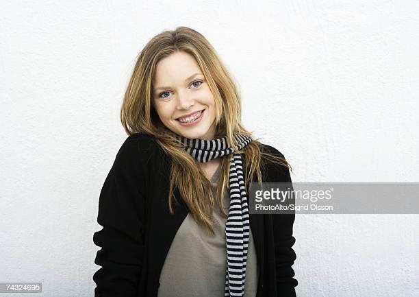 Teenage girl wearing scarf, smiling at camera