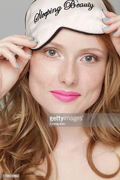 Teenage girl wearing Sleeping Beauty eye mask on head