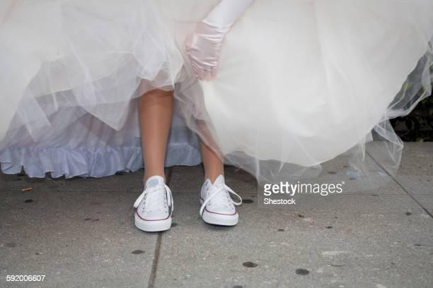 Teenage girl wearing sneakers under quinceanera dress