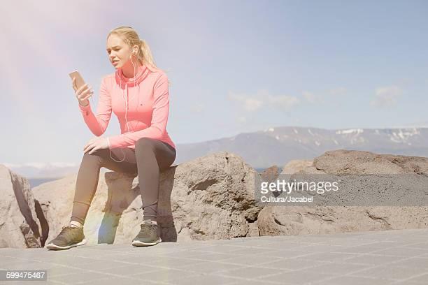 Teenage girl wearing sport clothing sitting on rocks looking at cellular phone, Reykjavik, Iceland