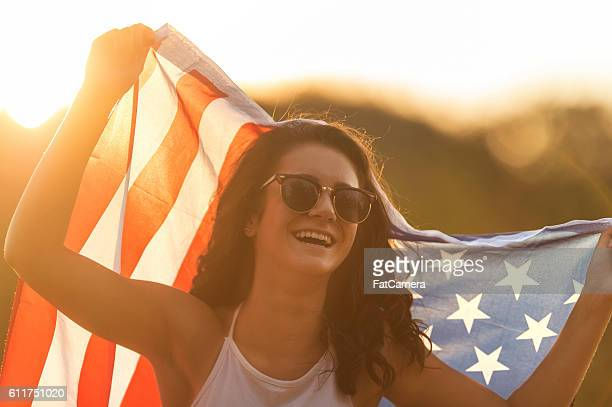 Teenage girl wearing sunglasses and holding an American flag