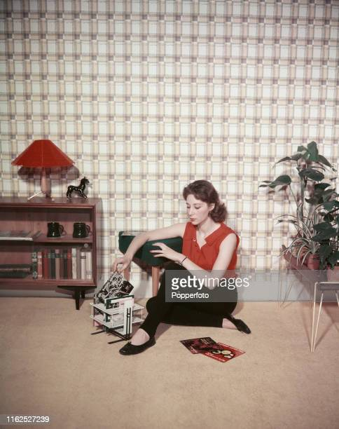 A teenage girl wearing tapered slacks and pumps arranging her collection of seven inch vinyl single records in to a storage rack in the living room...