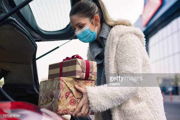 teenage girl wears a protective mask while shopping for christmas during covid-19 pandemic - feriado imagens e fotografias de stock