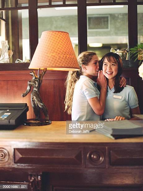 teenage girl(15-17) whispering in friends ear, standing behind desk. - trabalhadora de colarinho branco imagens e fotografias de stock