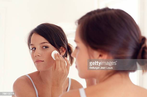 Teenage girl wiping face with pad