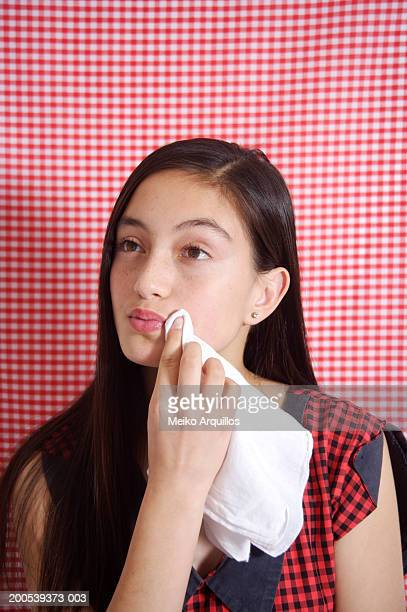 Teenage girl (13-15) wiping mouth with napkin