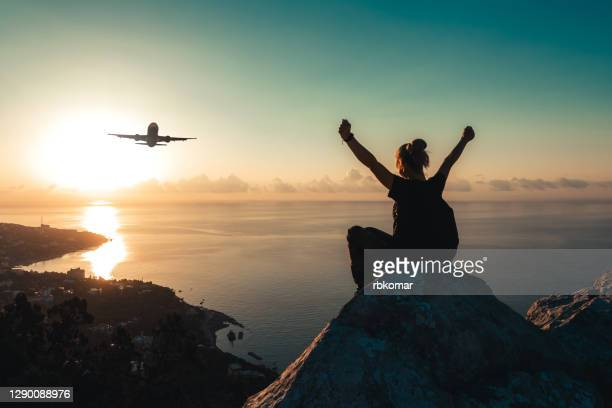 a teenage girl with a backpack sits on the edge of the peak of mountain and watches an airplane flying over the sea coast at sunrise - travel destinations stock pictures, royalty-free photos & images