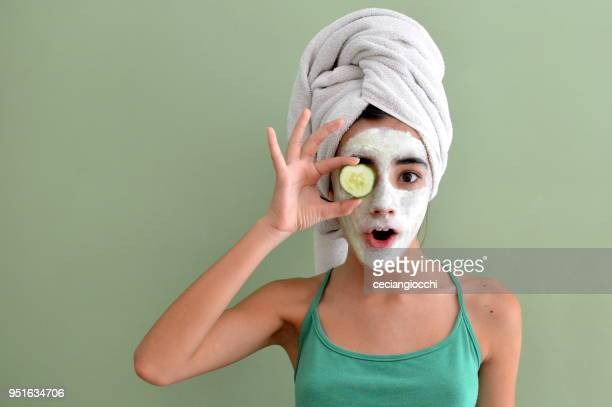 teenage girl with a face mask on holding a cucumber slice in front of one eye - キュウリ ストックフォトと画像