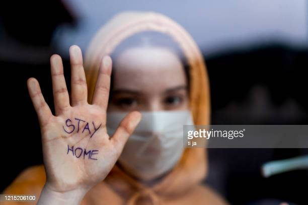 teenage girl with a surgical maks standing and looking through the window and showing 'stay home' message written on her hand - illness prevention stock pictures, royalty-free photos & images