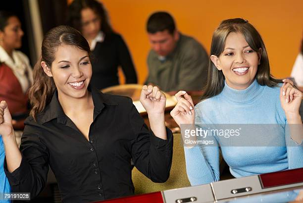 teenage girl with a young woman playing on slot machines - teen pokies stock photos and pictures