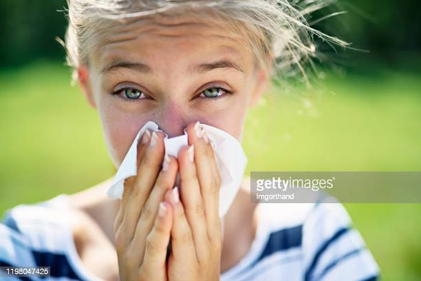 teenage girl with allergy blowing nose - bloodshot stock pictures, royalty-free photos & images