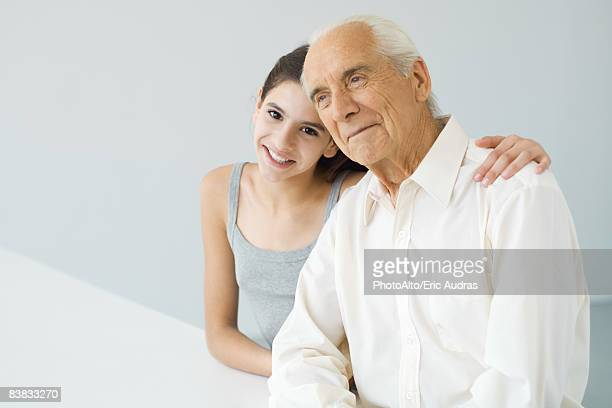 Teenage girl with arm around her grandfather's shoulder, senior man looking away