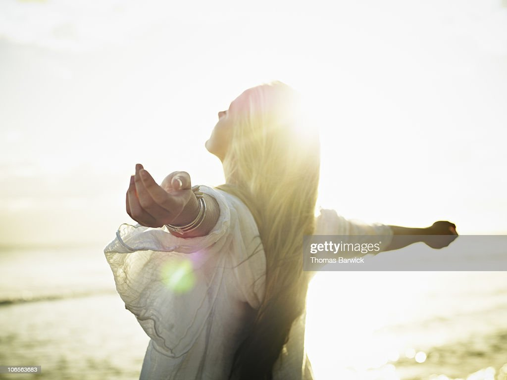 Teenage girl with arms outstretched at sunset : Stockfoto