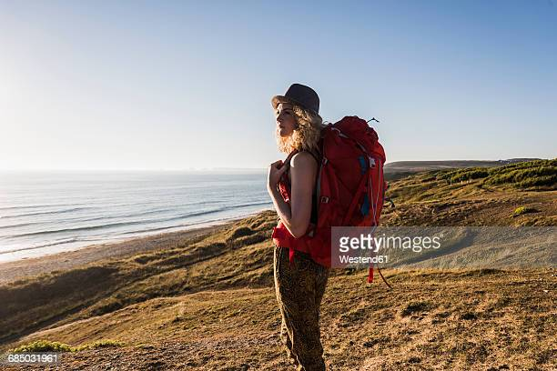 teenage girl with backpack at seaside looking at distance in the evening twilight - rucksacktourist stock-fotos und bilder