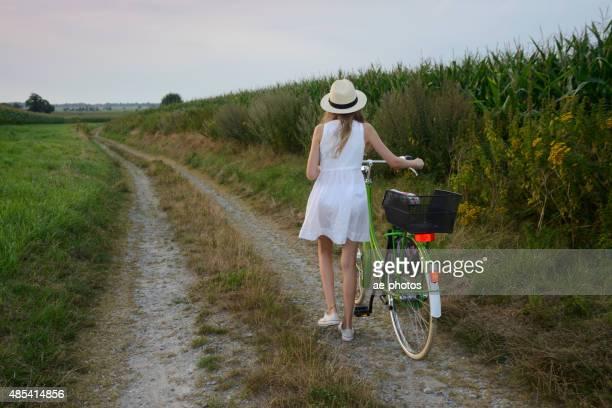 Teenager-Mädchen mit dem Fahrrad auf der Schotterstraße in cornfield