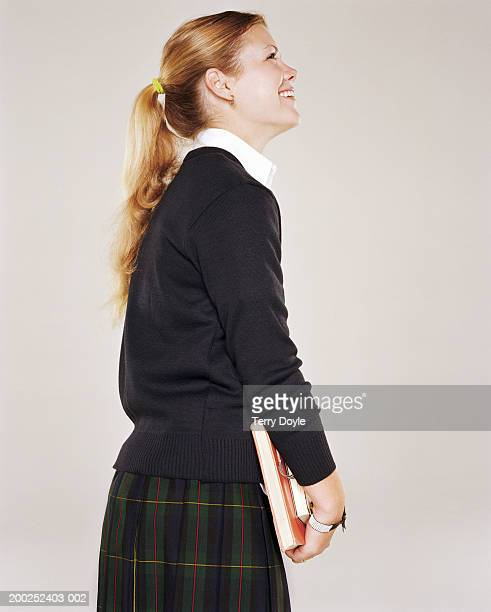 Teenage girl (14-16) with books wearing school uniform, side view