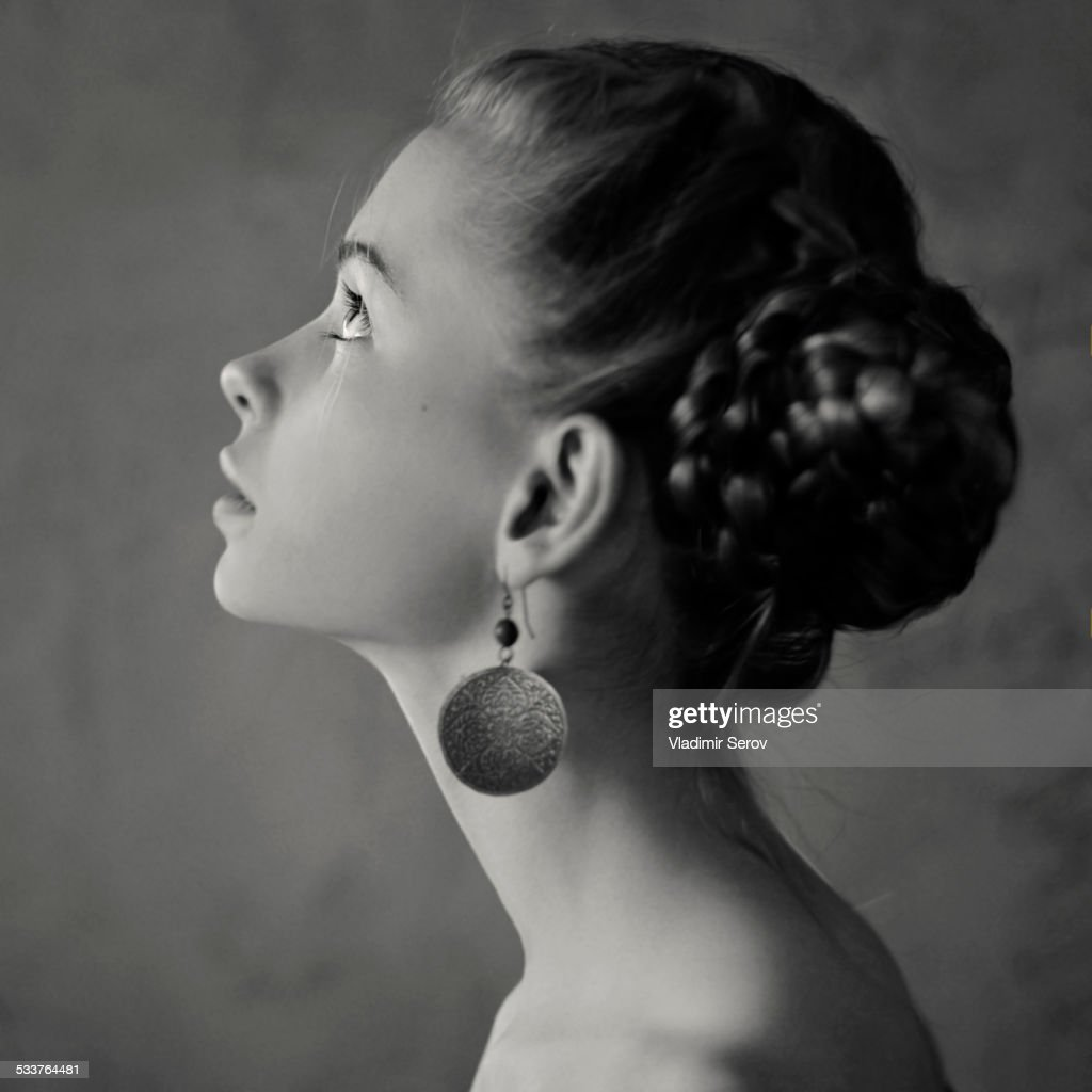 Teenage girl with braided hair wearing dangling earrings : Foto stock