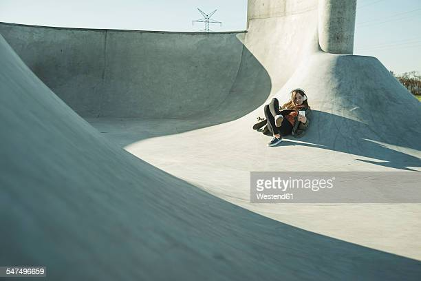 Teenage girl with cell phone and headphones in skatepark