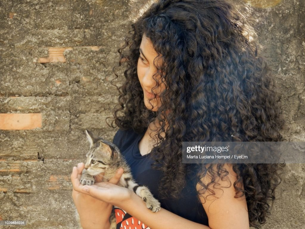 Teenage Girl With Curly Hair Holding Kitten By Wall Stock Photo