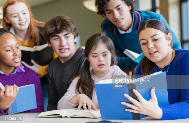 teenage girl with down syndrome and friends reading - learning disability stock pictures, royalty-free photos & images