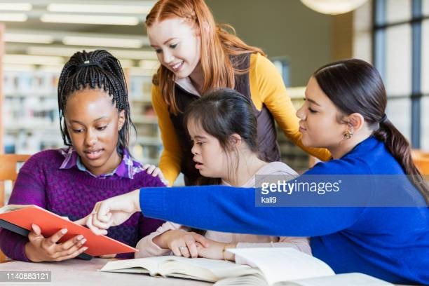ダウン症候群と友人を勉強している十代の少女 - ティーンエイジャーのみ ストックフォトと画像