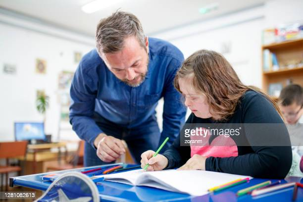 teenage girl with down syndrome drawing at class - learning disability stock pictures, royalty-free photos & images
