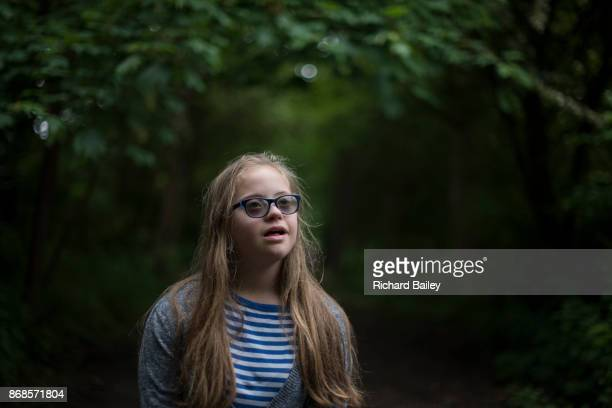 Teenage girl with Down syndrome in woods.