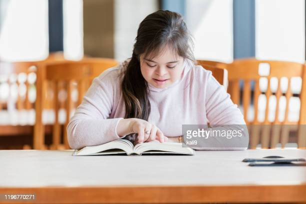 teenage girl with down syndrome reading in library - learning disability stock pictures, royalty-free photos & images