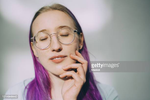 teenage girl with eyes closed standing against wall - purple hair stock pictures, royalty-free photos & images