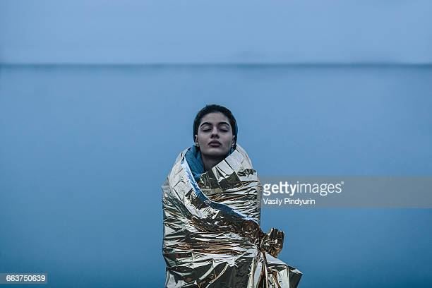 teenage girl with eyes closed wrapped in golden plastic against lake - extreme weather stock photos and pictures