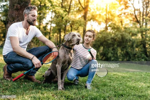 teenage girl with father and dog on meadow