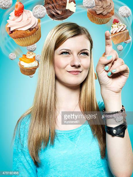 teenage girl with flying cupcakes around her head, composite - menschlicher finger stock-fotos und bilder