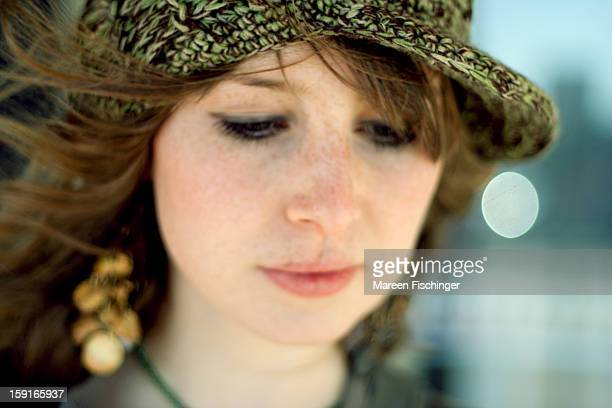 Teenage girl with hat, looking down, soft focus