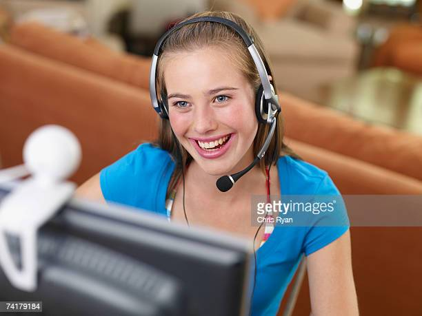 Teenage girl with headset looking at computer monitor smiling