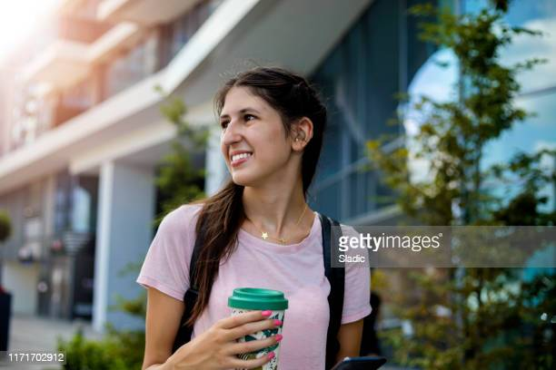 teenage girl with hearing aid walking on city street - hearing aid stock pictures, royalty-free photos & images