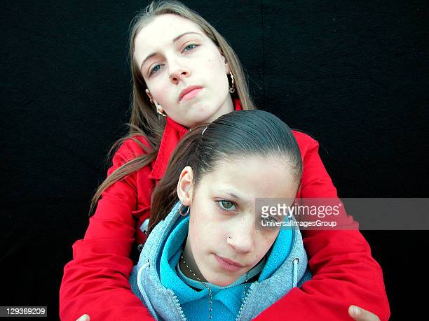 Teenage girl with her arms around a younger girl London 2000