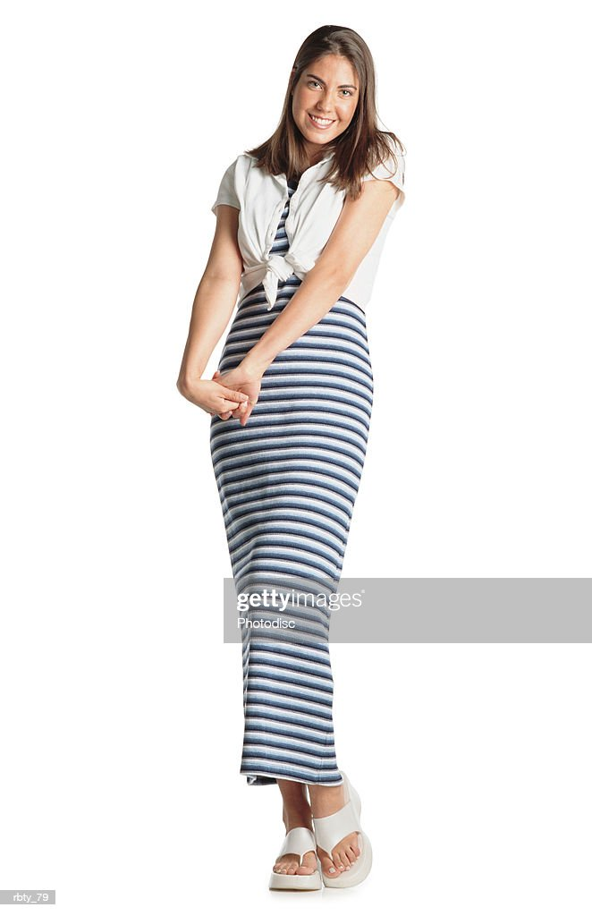 teenage girl with long brown hair wears a striped dress with a white shirt and white sandles crosses her hands as she smiles at the camera : Foto de stock
