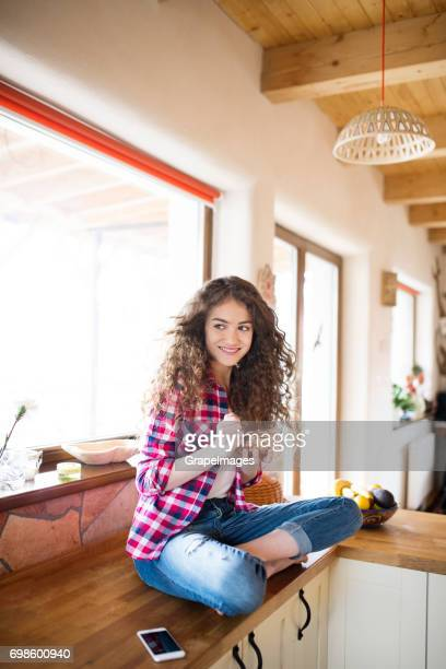 Teenage girl with long curly hair at home eating granola, smart phone next to her
