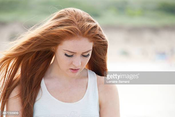 Teenage girl with long red hair blowing in wind