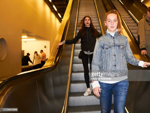 teenage girl with long red hair brown eyes and freckles and friend with black hair and brown eyes traveling london wearing coats walking down escalator steps in motion looking at the camera flash of camera is lighting image - nostalgia stock pictures, royalty-free photos & images