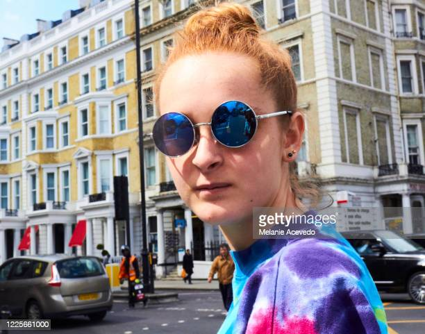 teenage girl with long red hair brown eyes and freckles body turned towards camera wearing circle glasses with blue reflection hair worn up in a bun and tie dye shirt looking towards the camera - only teenage girls stock pictures, royalty-free photos & images