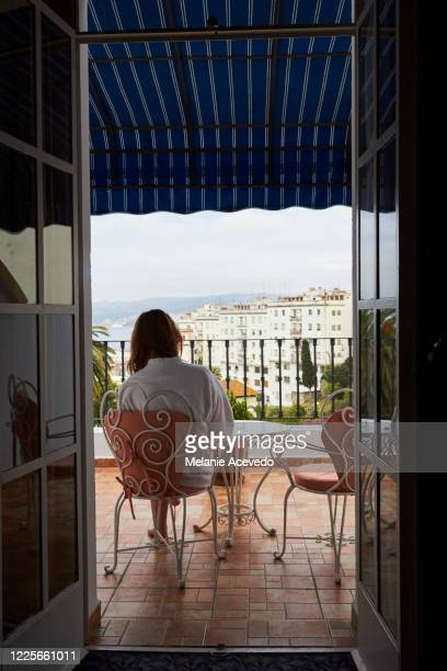 teenage girl with long red hair brown eyes and freckles on hotel balcony sitting on chair looking out at overlooking beautiful skyline - balcony stock pictures, royalty-free photos & images