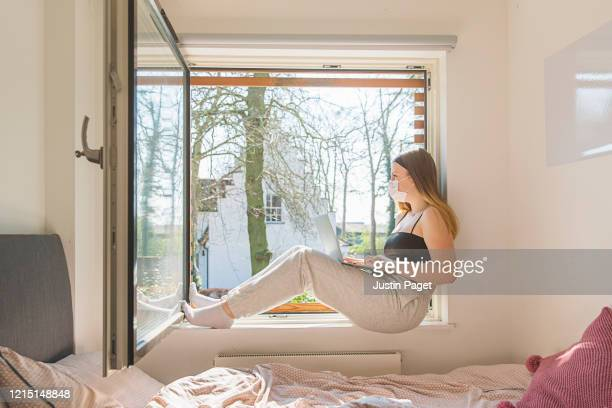 teenage girl with mask looking out of window - tracksuit bottoms stock pictures, royalty-free photos & images