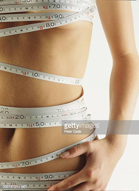 Teenage girl (16-18) with measuring tape wrapped  around body