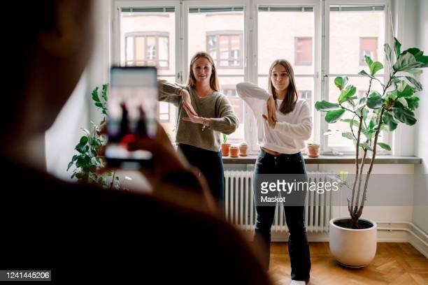 teenage girl with mobile phone filming female friends dancing against in living room - tipo di danza foto e immagini stock